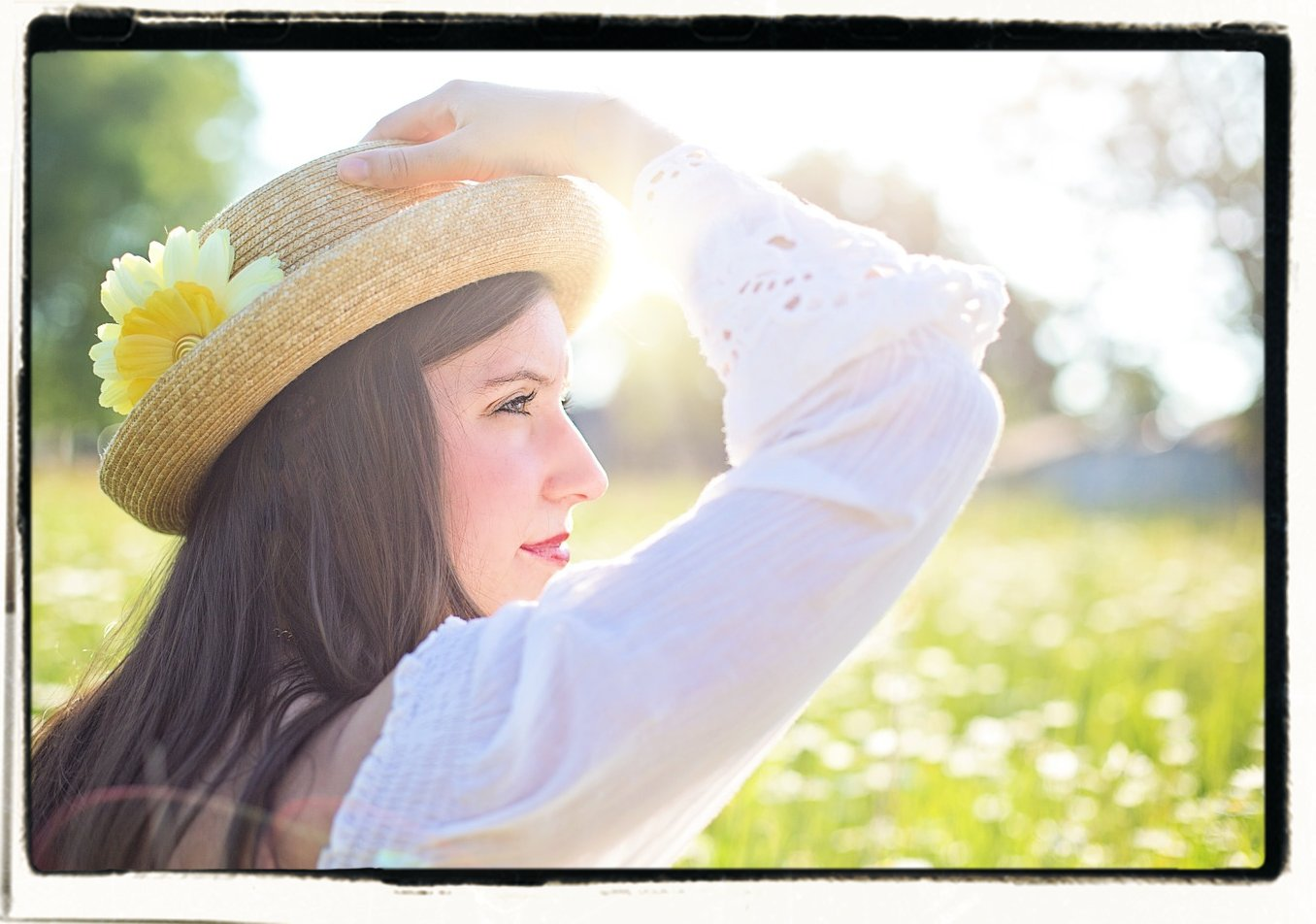 woman in a field of flowers wearing a hat